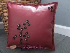 Hematite and glass beaded flowers on a dark red upholstery leather front and black organic leather back
